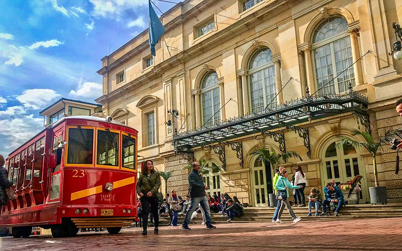 A red tram passes in front of the golden stone facade of the Teatro Colón in Bogota on a sunny day © Jacqui de Klerk / Lonely Planet