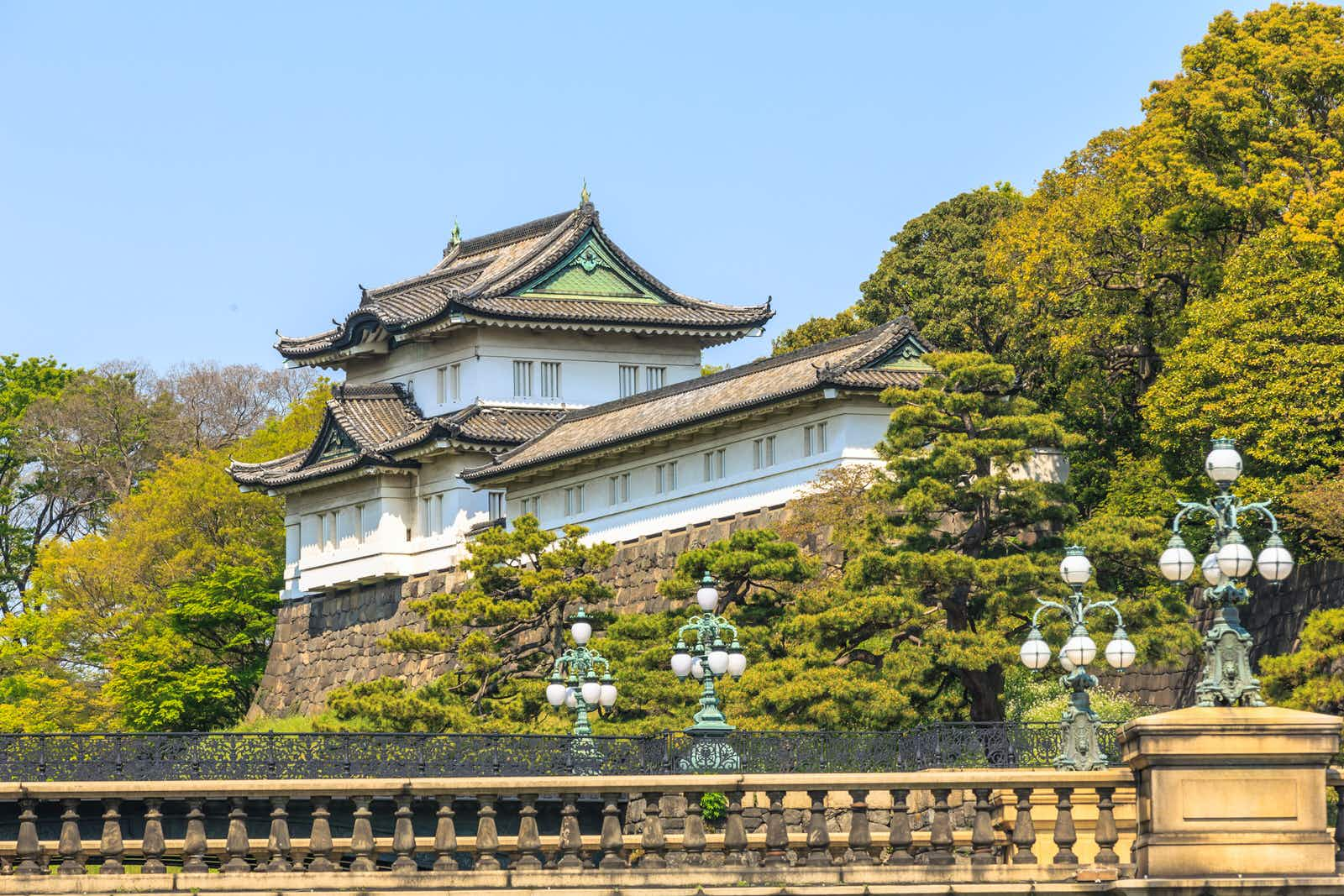 With trees on either side and a balustrade in front, the Imperial Palace in Tokyo, Japan, stands beneath a blue sky, painted white with ornate eaves