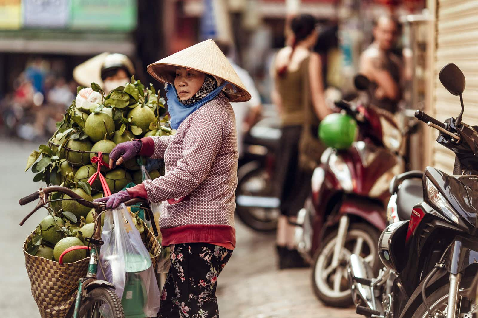 A Vietnamese woman in a conical hat sells fresh green coconuts on the street of Ho Chi Minh city in Vietnam,