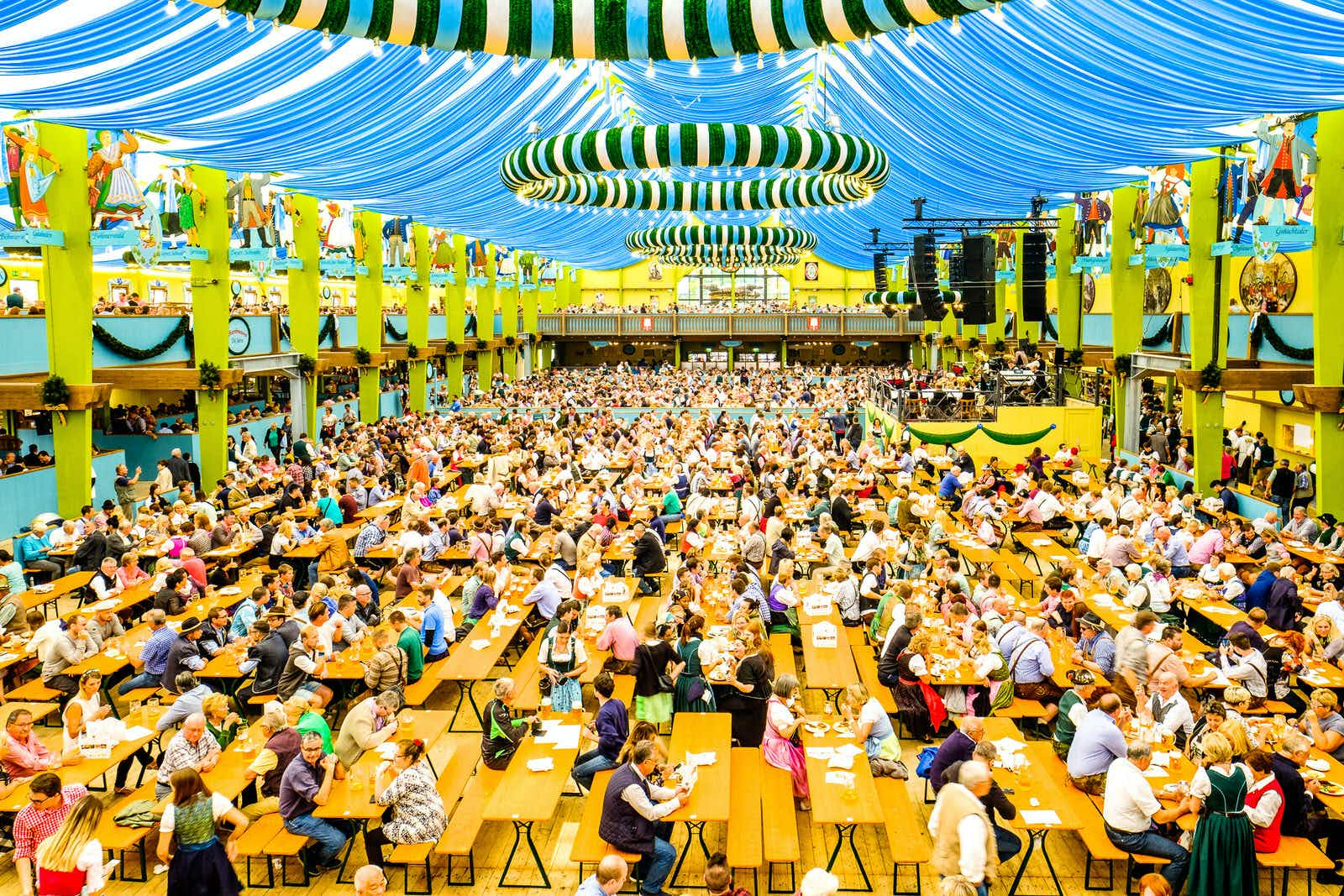 People in the 'Spaten' beer tent at Oktoberfest in Munich. The huge tent, that houses hundreds of tables, has a colourful blue ceiling and striped decorations.