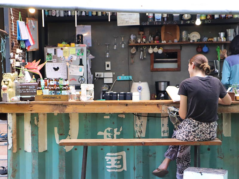 Woman reading a book at the outdoor bar of The Yard hostel