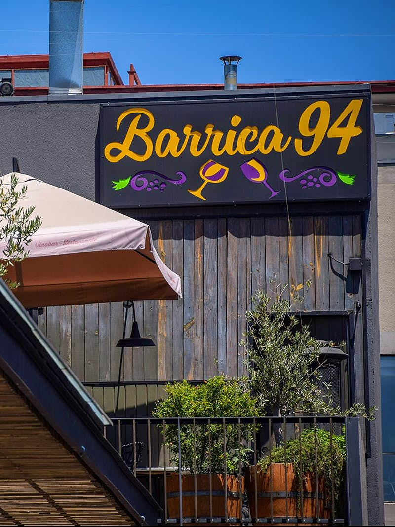An external shot of the Barrica 94 sign, which features yellow cursive text, purple grapes, and two wine glasses