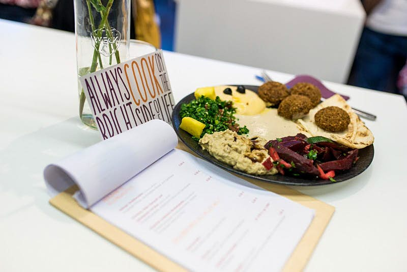 A plate of falafel, hummus and salad next to Über den Tellerrand cafes menu, in Munich. There is also a sign reading 'always cook on the bright side of life' © Über den Tellerrand GmbH