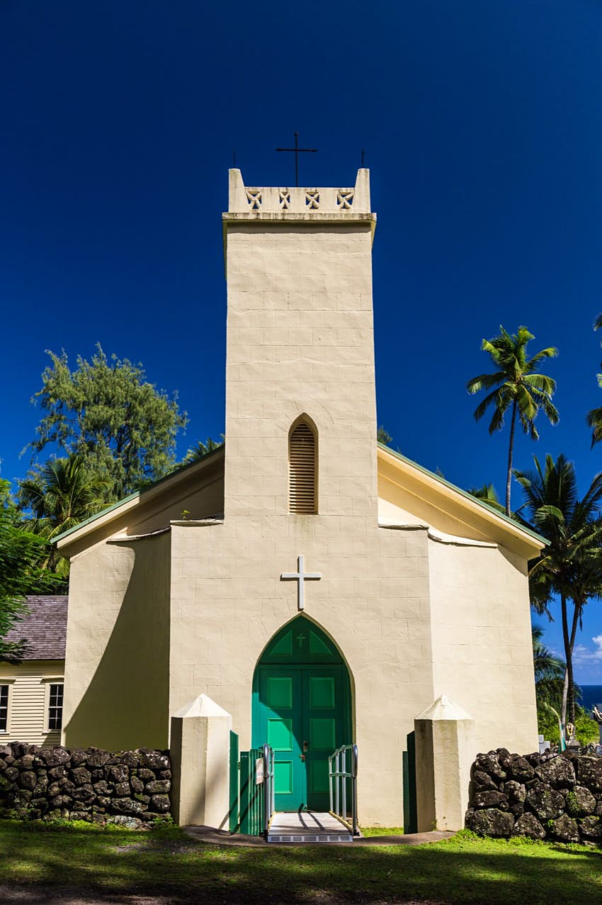 A small, cream-colored church with a bright green arched doorway and a central, rectangular steeple