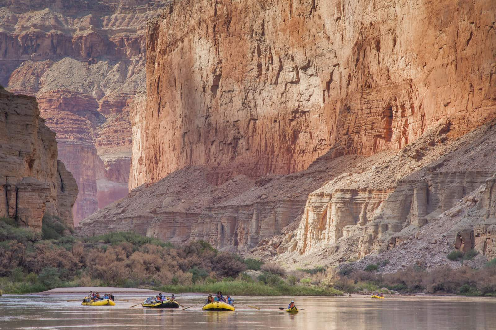 Whitewater rafts and a kayak drift on a calm part of the Colorado River in the Grand Canyon, as sheer rock walls fill the frame behind.