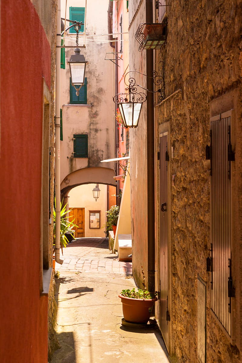 Looking down a narrow alleyway in Montemarcello, with glass lanterns and green shutters. There are some potted plants on the paved alley. The wall on the left is smooth and painted orange, the wall on the right is made from exposed, beige stones.