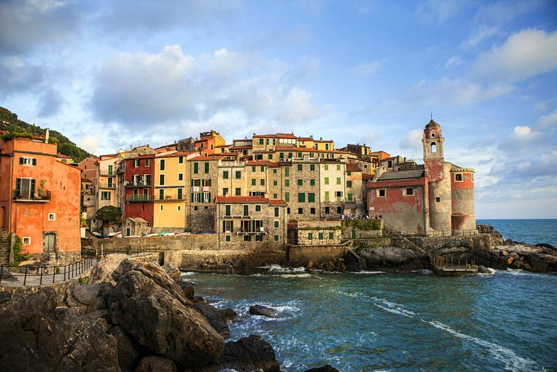 Tellaro's small harbour on a slightly overcast day. Narrow brick buildings are crammed in, side by side on a rocky outcrop. The buildings are warm yellows, beige, orange and terracotta. Closest to the sea there is a faded pink church. The sea is restless.