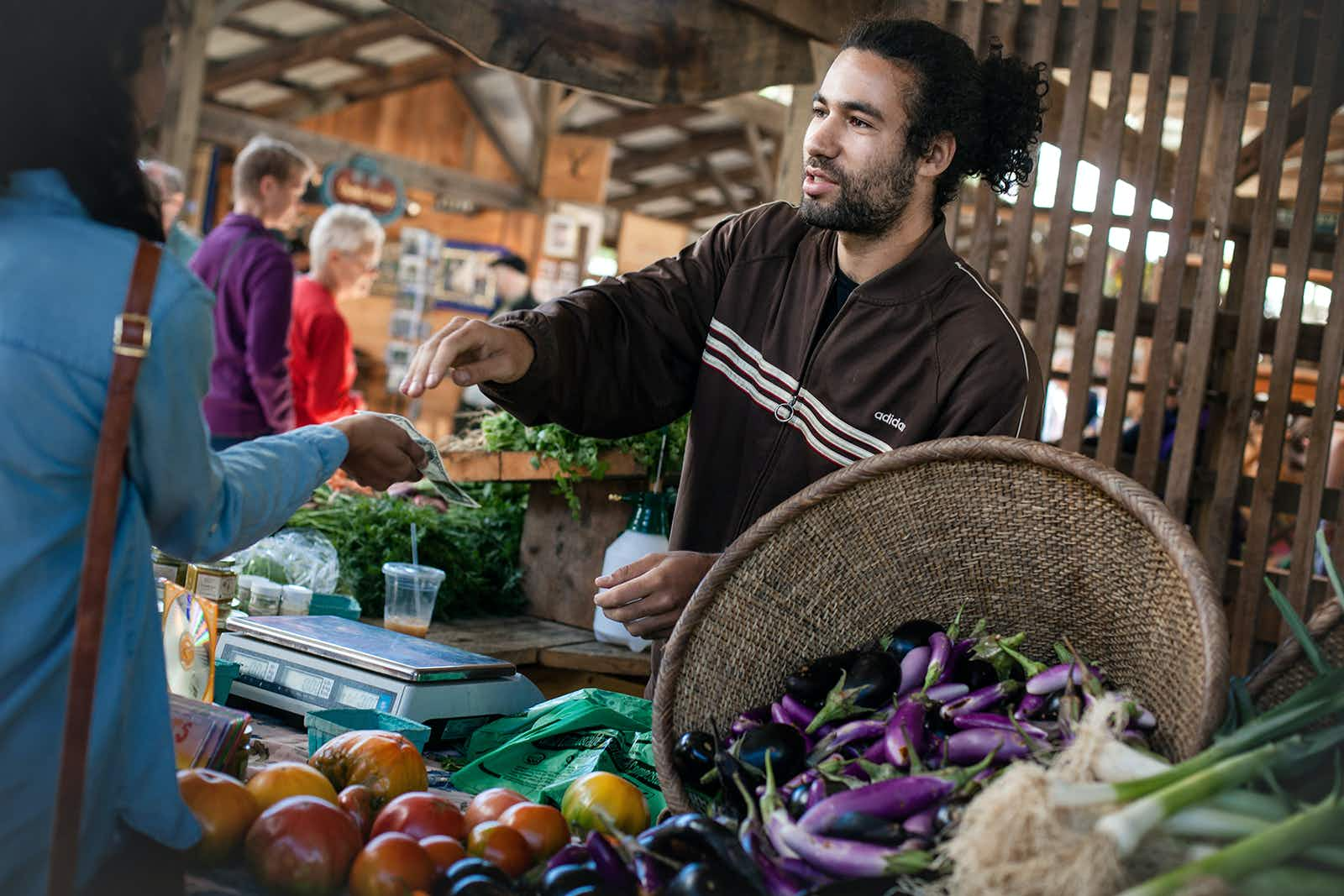 A man smiles and hands change to a woman over a stall of fresh local vegetables (eggplant, etc) at a farmer's market