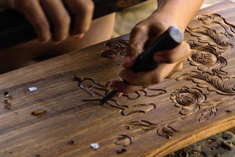 A man works on a wood carving to be inlaid with mother-of-pearl at Kim Bong