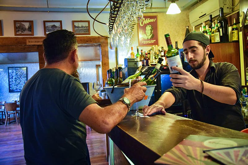 A bartender pours a glass of wine for a patron at a wine bar in Santiago, Chile
