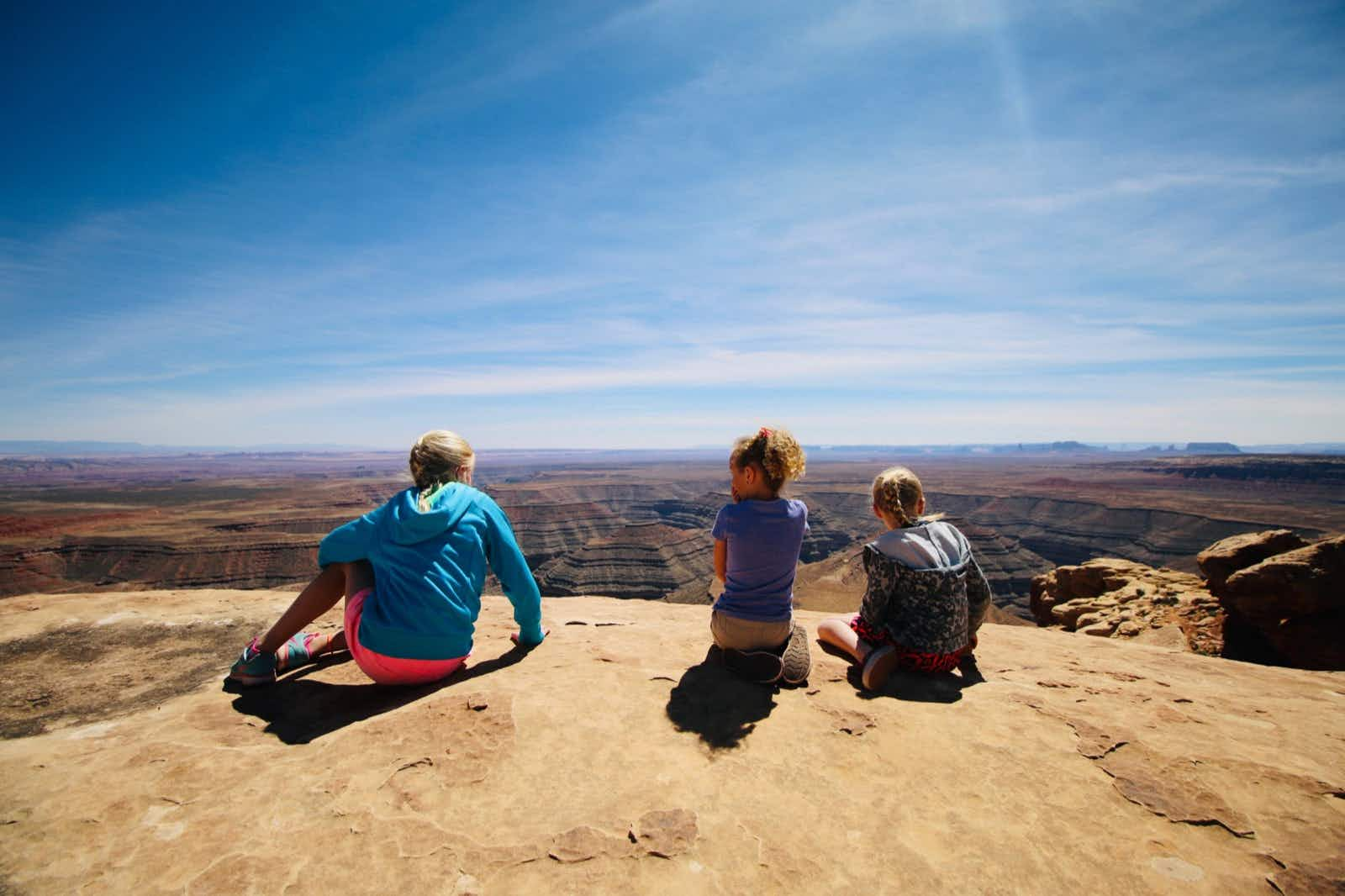 Three children sit on the edge of a rocky overlook, with canyons spread out below them
