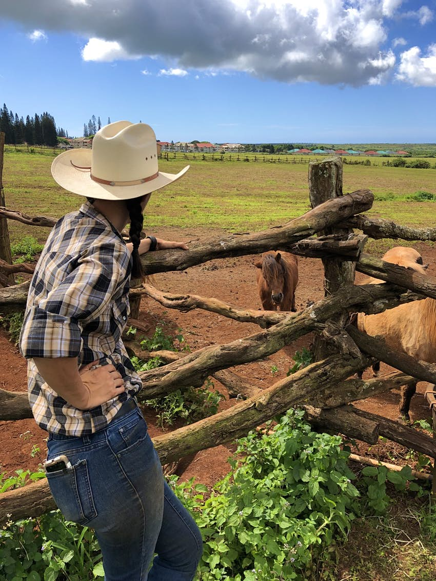 A woman with braided hair, a cowboy hat, jeans and a plaid shirt leans against a wooden fence and looks out at a flat expanse of land