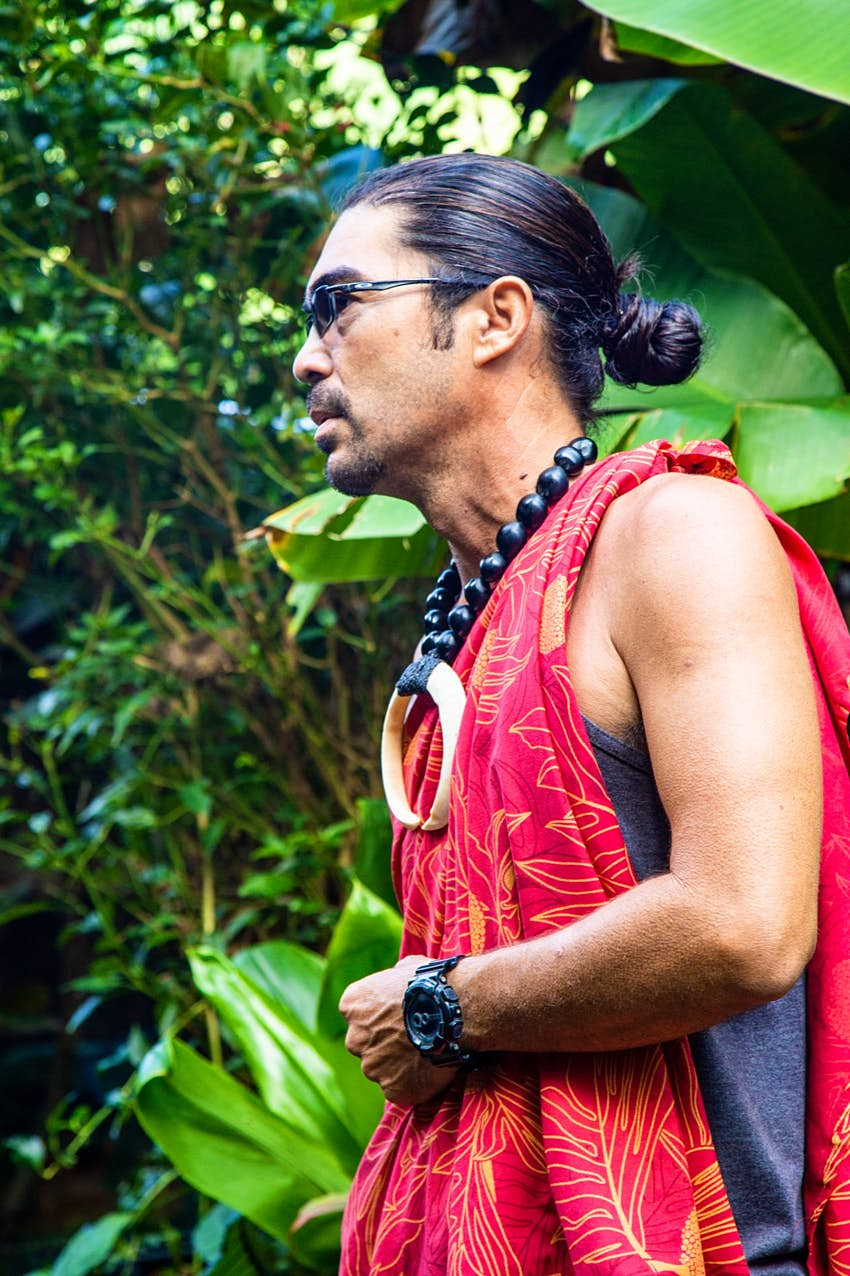 A man leads a group through a tropical jungle, dressed in a traditional Hawaiian tunic with a large necklace and his hair in a tight bun. He also wears modern sunglasses and a heavy modern watch