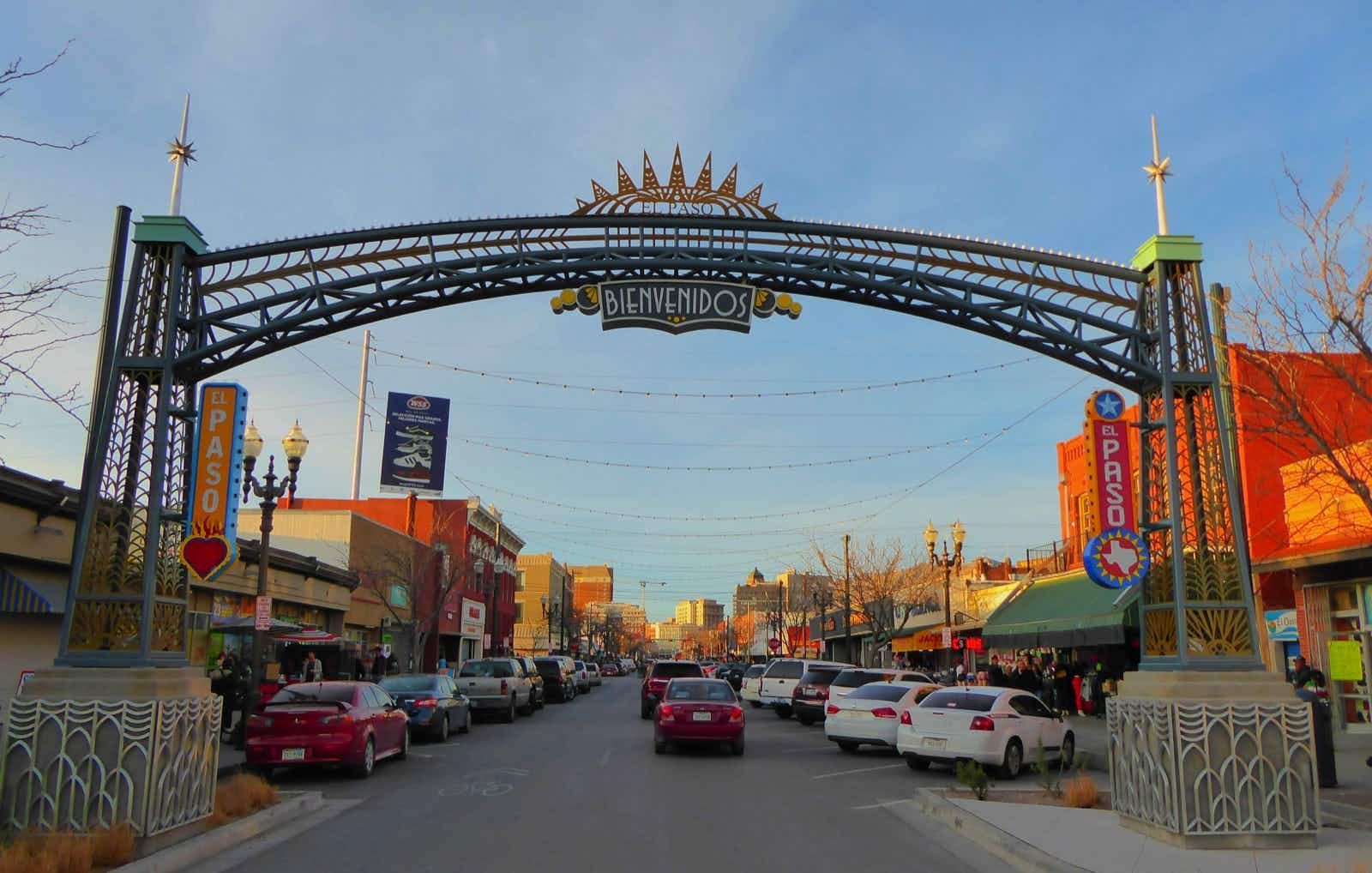 A city street, with shops along each side, is dominated by a colorful archway in the foreground that welcomes visitors to El Paso, Texas