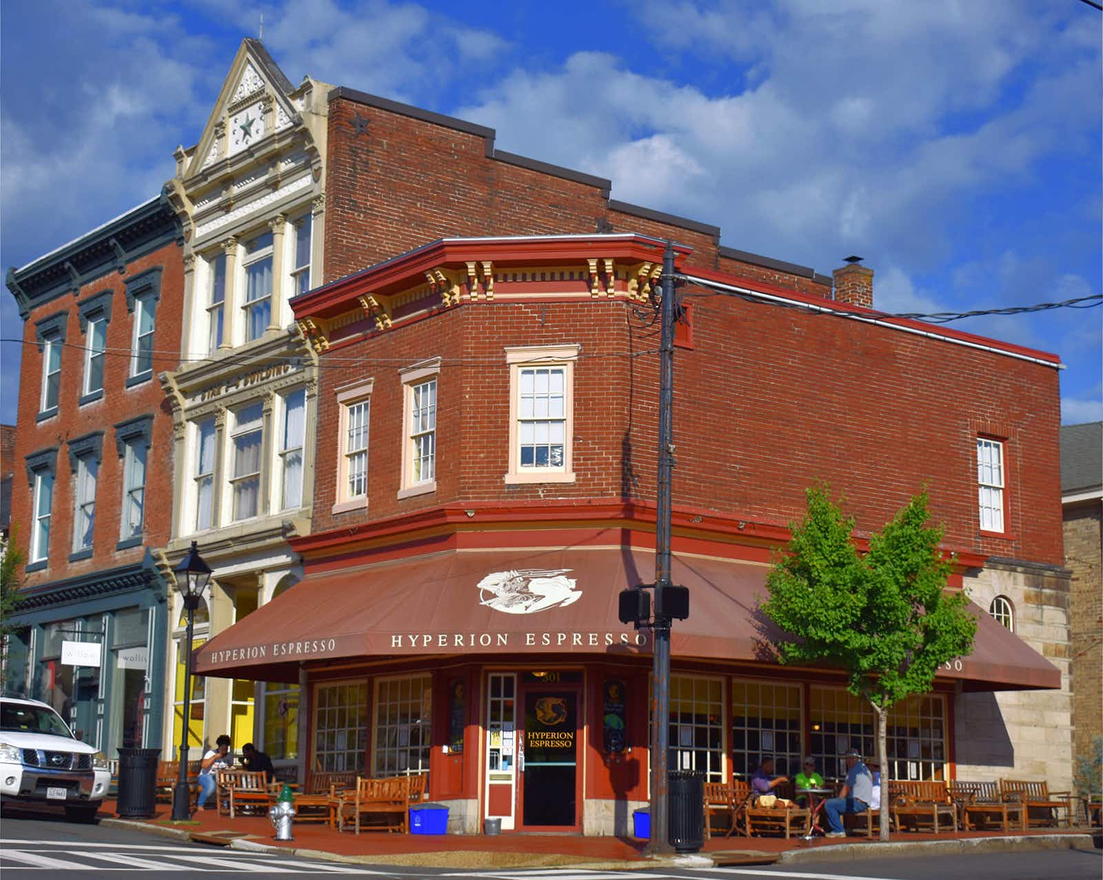 """A corner shop in red brick with a maroon awning bearing the words """"Hyperion Espresso"""" on a sunny day in Virginia"""