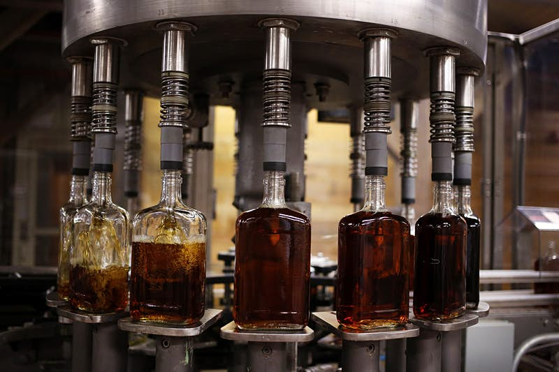 Features - Bottles of single barrel bourbon are filled on the bottling line at a distillery