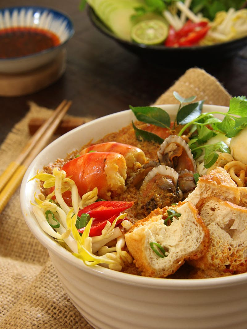 Peranakan laksa served in a bowl, accompanied with chili sauce and extra vegetables