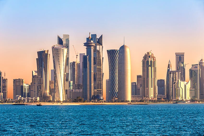 The skyline of Doha, Qatar, as seen from the water at sunset; numerous skyscrapers have unique, twisting shapes.