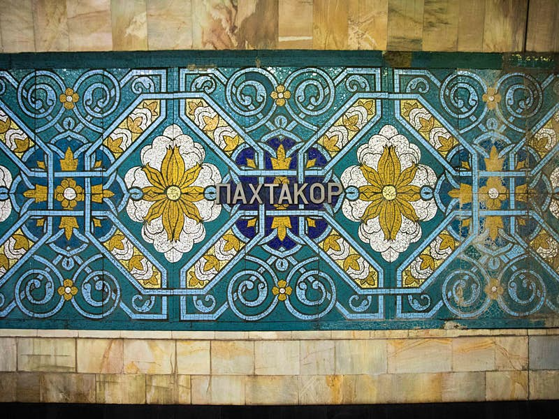 The walls of Pakhtakor station bearing the station name surrounded by ornate blue and green Uzbek mosaics.