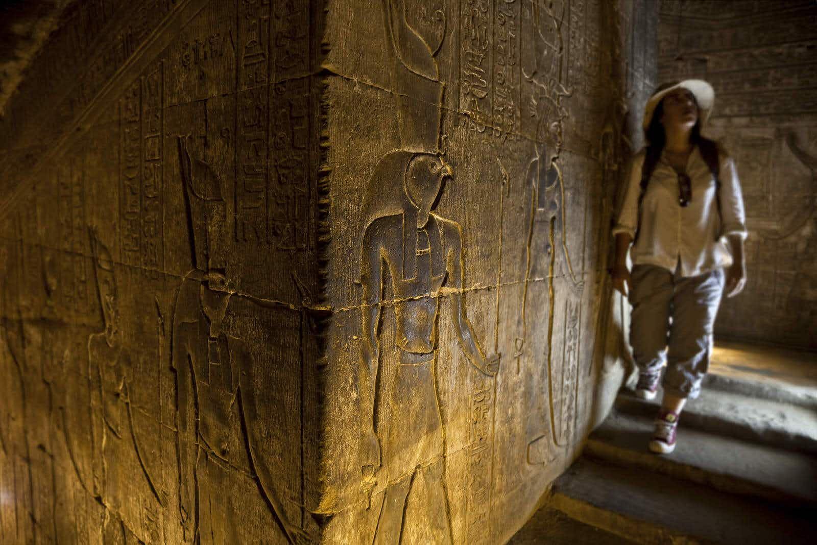 Woman in temple looking at hieroglyphics. Edfu temple.