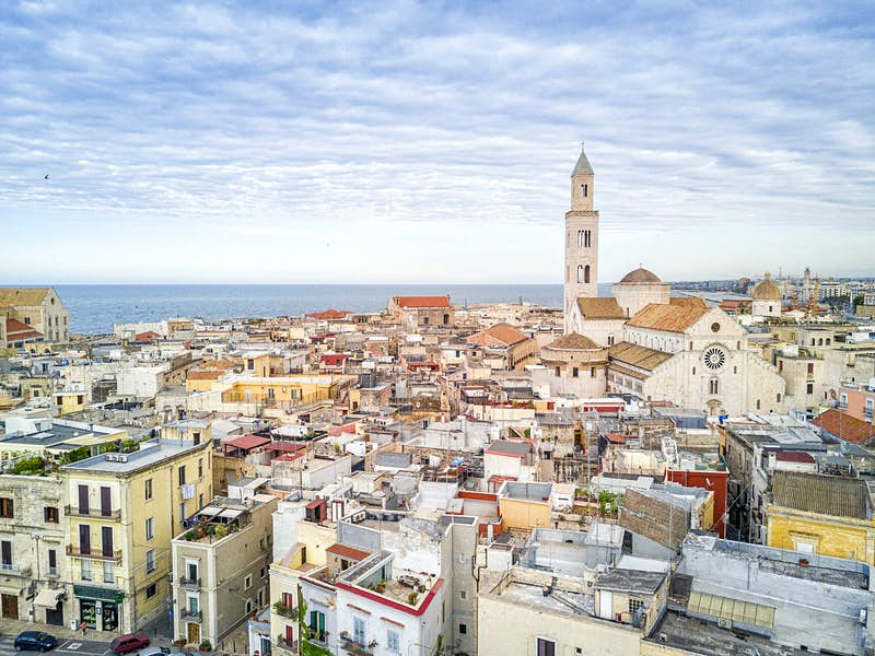 A view of the tightly packed buildings of Bari's Old Town, with Basilica di San Nicola on the right and the sea in the distance