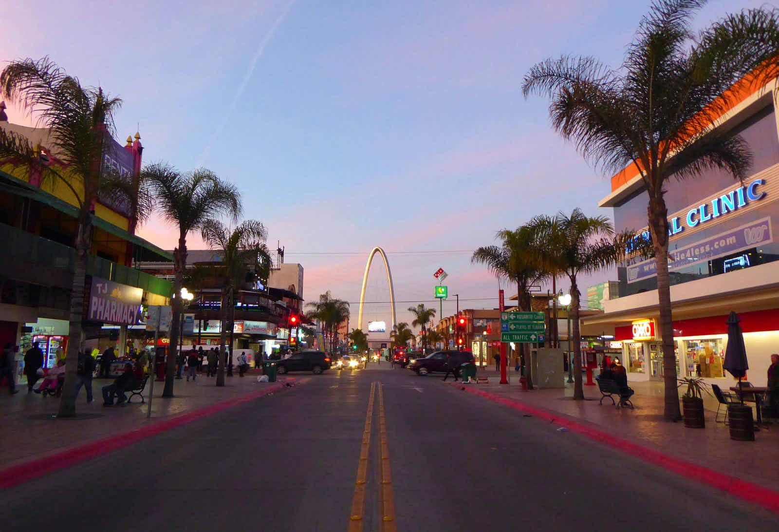 An empty street lined with palm trees with an arch at one end under a blue sky dotted with pink clouds