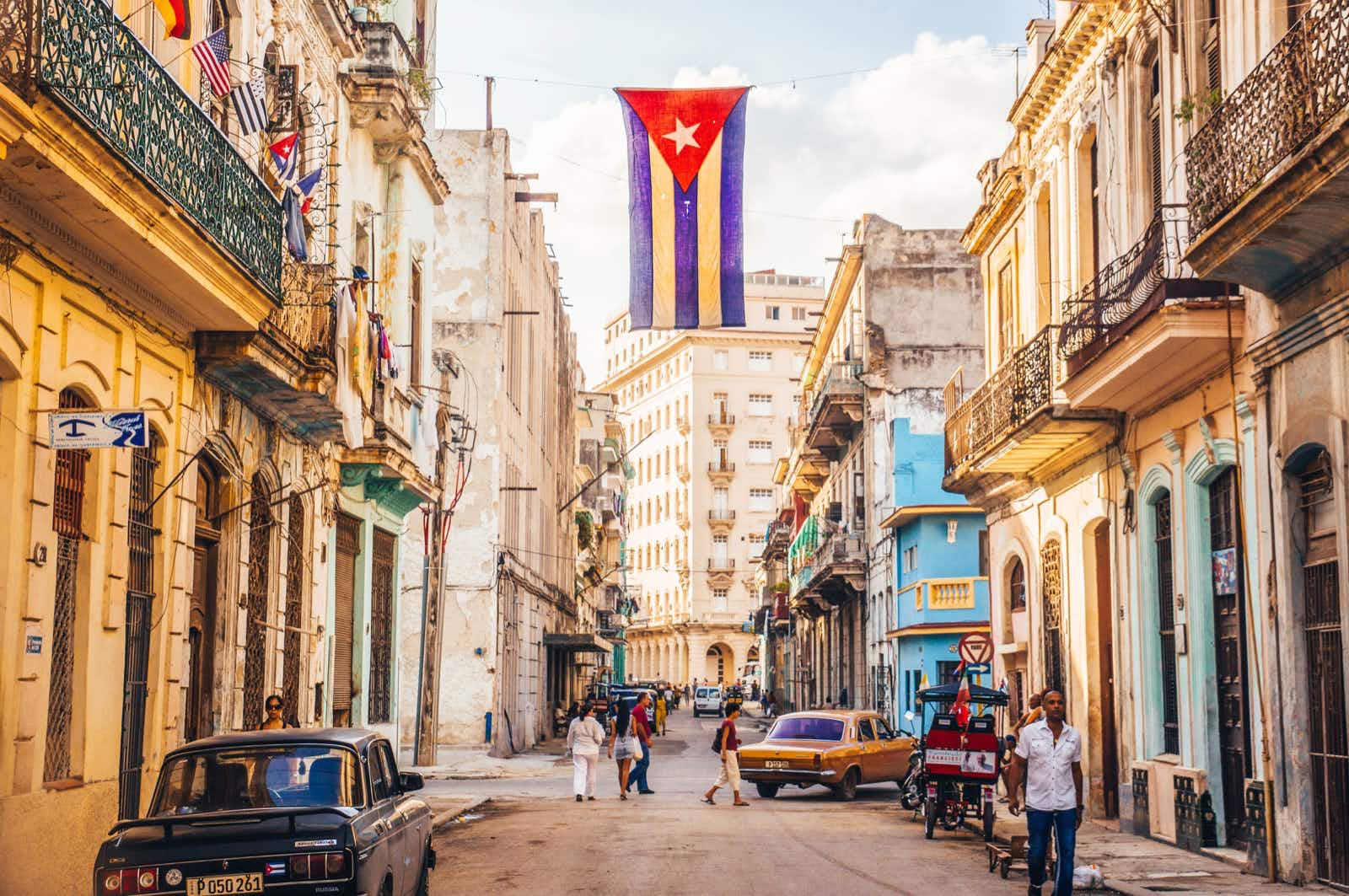 Havana, Cuba in December 2015: A cuban flag with holes waves over a street in Central Havana. La Habana, as the locals call it, is the capital city of Cuba; Shutterstock ID 412724059; Your name (First / Last): William Broich; GL account no.: 65050; Netsuite department name: Editorial ; Full Product or Project name including edition: How to travel responsibly in Havana
