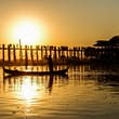 A boatman rows his way past U-Bein bridge at sunset