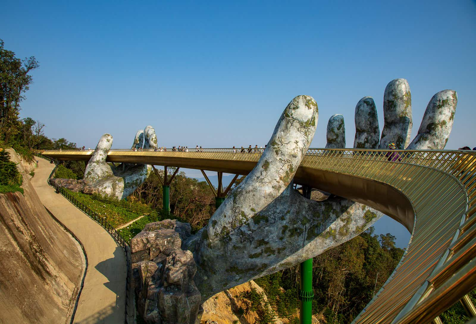 People stroll across the Golden Bridge in Ba Na Hills, which appears to be supported by giant hands
