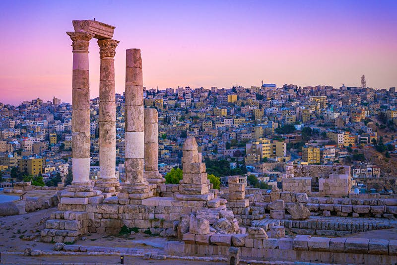 Several Roman columns stand tall and alone atop a hill, with the city in the distance as a backdrop; the sky is an incredible shad of pink and purple; Free things to do in Amman, Jordan