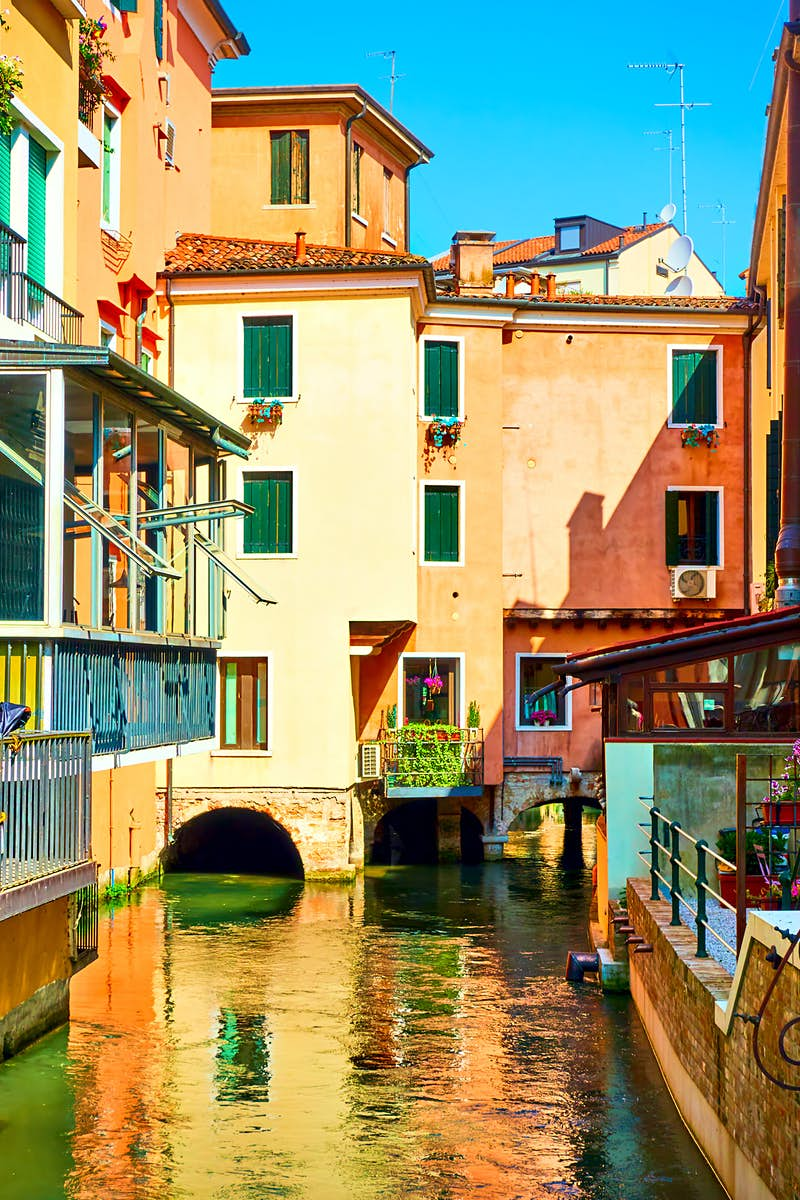 View along a canal in Treviso, with colourful buildings reflected in the water
