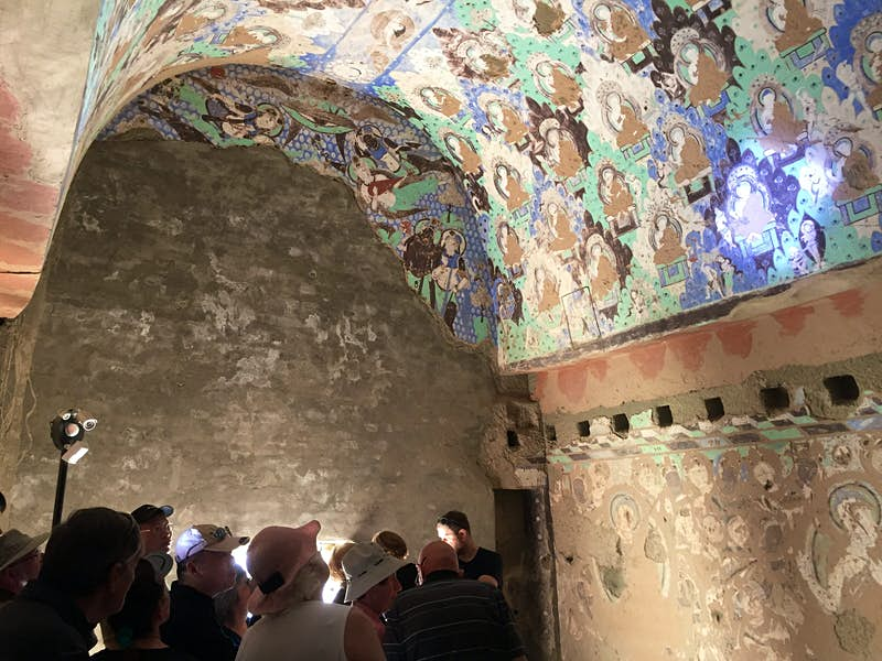 A group of visitors huddled below left stare up at an arched cave ceiling with blue, green and brown Buddhist murals illuminated by spotlights.
