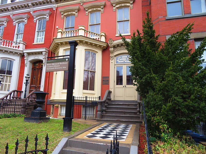 A checkerboard patterned walkway leads to a red row house with a cream-colored dormer window