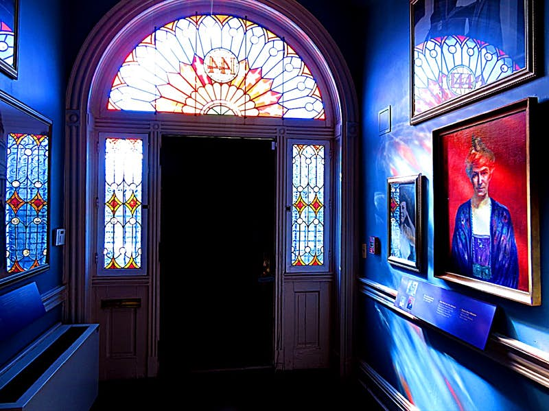 Sunlight streams through stained glass windows into a dark foyer with artwork celebrating women