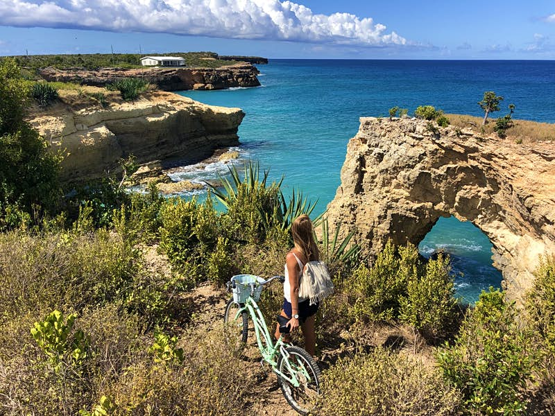 A woman with a bike stands stands on edge overlooking The Arch on the West End on Anguilla