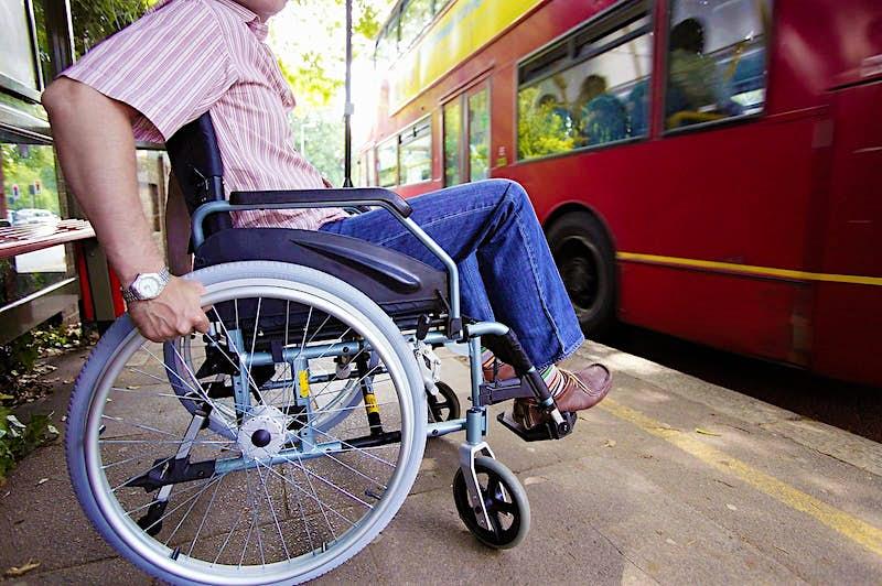 A wheelchair user waits for a London bus