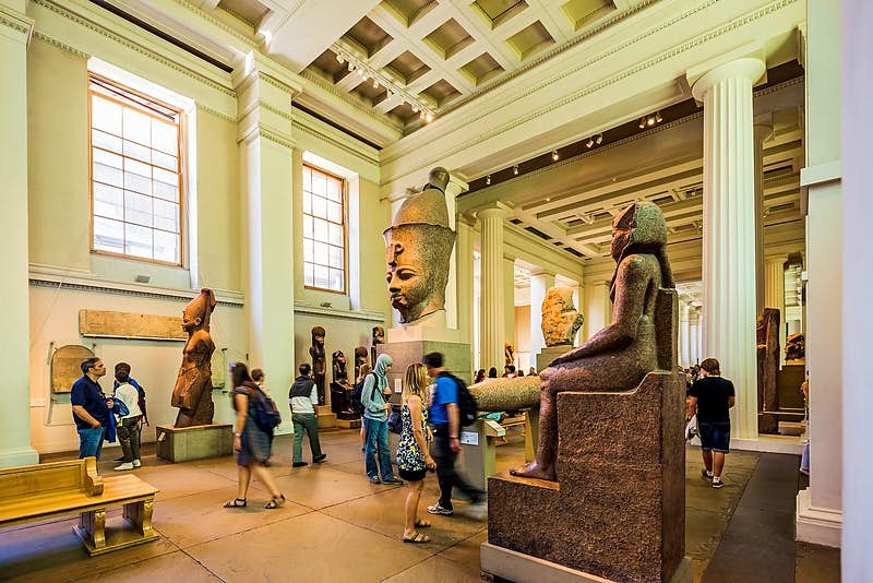 Visitors wander between statues in the British Museum's Egyptian sculpture gallery