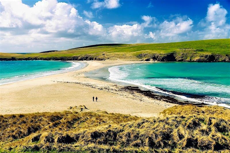 A couple walk across an empty beach in Shetland