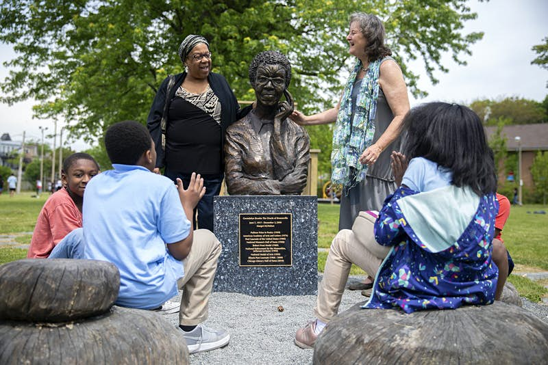 A group of people gather around Gwendolyn Brooks' statue in the Chicago park named after her