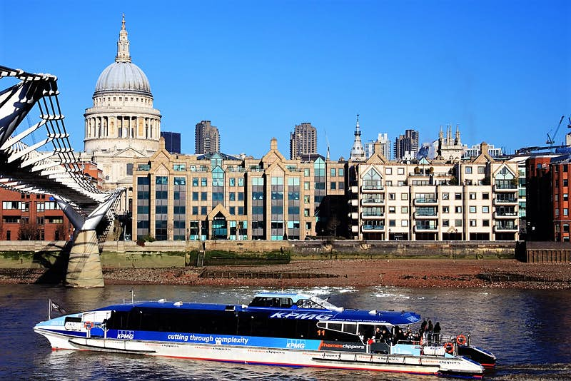 A Thames Clipper boat glides past St Paul's Cathedral on the river