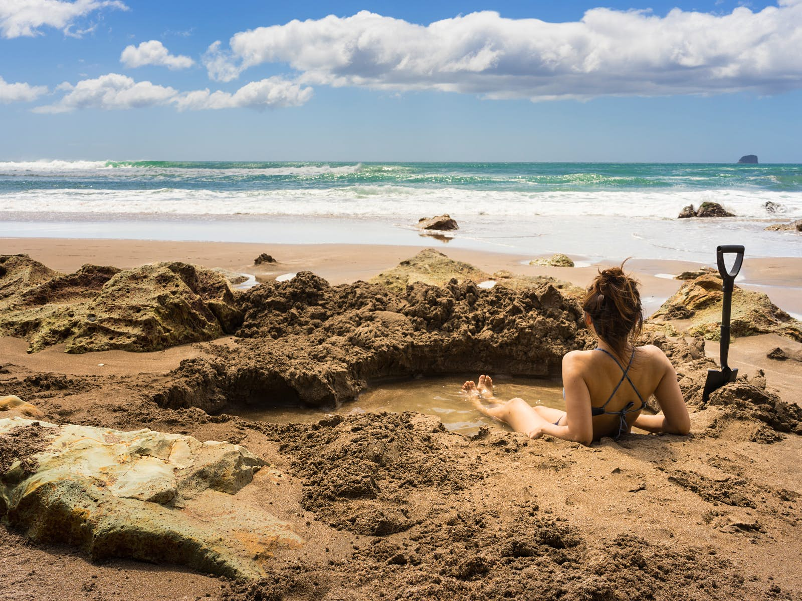 A woman sitting in a self-dug hot pool on Hot Water Beach, New Zealand