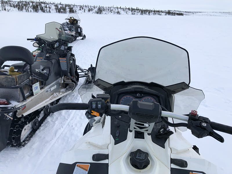 Looking down on a white snowmobile from the saddle, with a line of trees ahead in the Northwest Territories