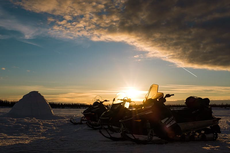 The sun goes down behind a row of snowmobiles parked next to an igloo in the Northwest Territories