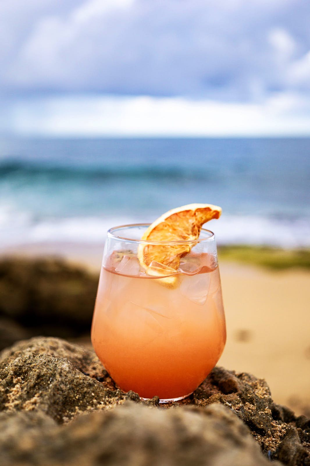 A peach-colored cocktail with an orange slice resting on the rim sits on a rock on the beach. In the background, waves crash onto the shore on a cloudy day. More and more San Juan restaurants are making creative cocktails a priority.