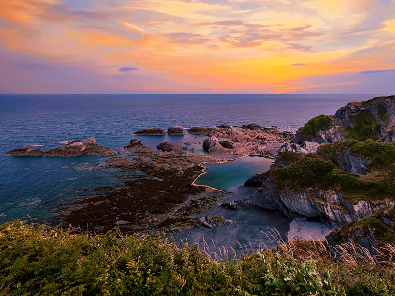 A sunset over the rocks pools of Tunnels Beaches in Devon
