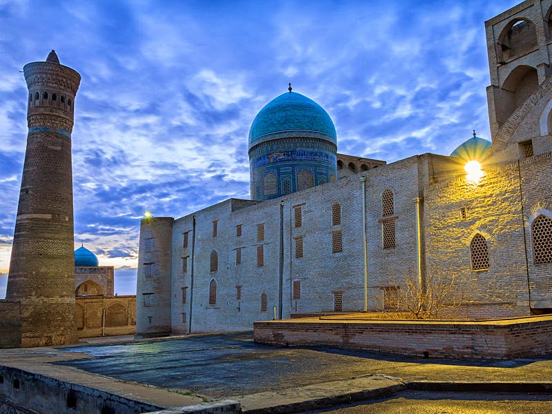 The blue dome and brown mud structures of the Kalon Mosque and minaret under cloudy, dusk skies.