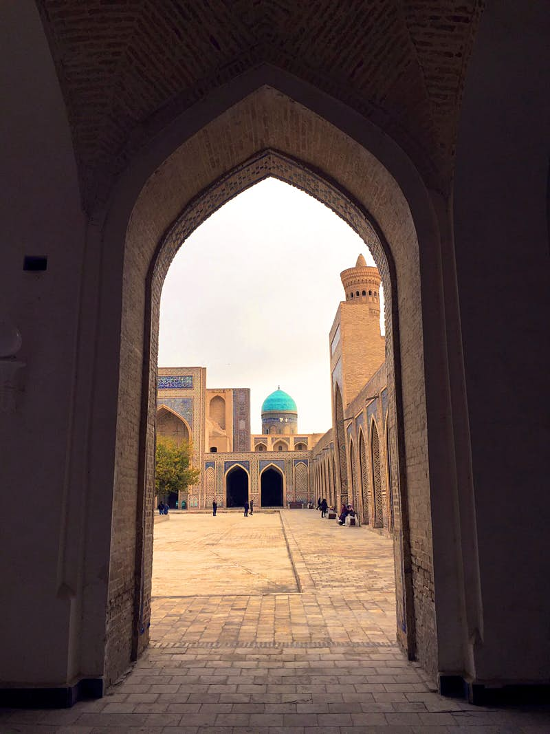 The inner courtyard of Kalon Mosque with blue dome and minaret as seen through a pointed arched doorway.