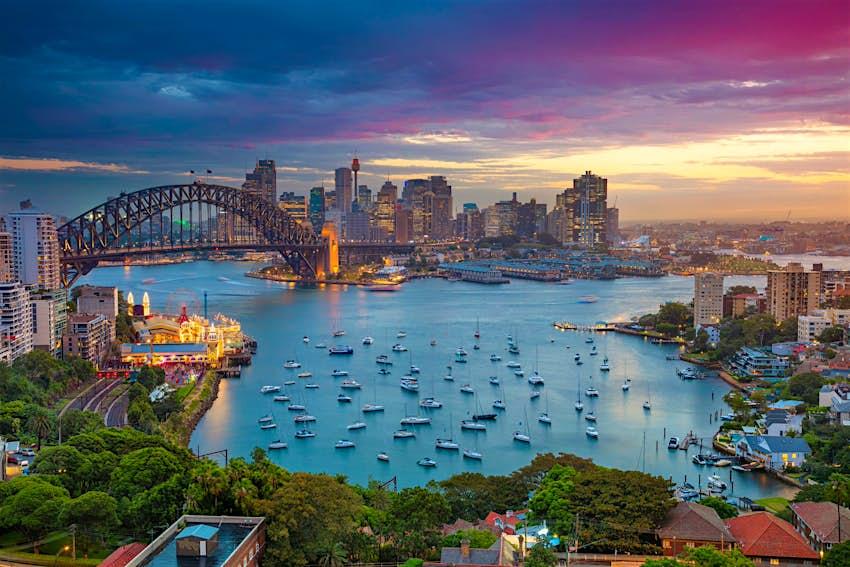 Cityscape image of Sydney, Australia with Harbour Bridge and Sydney skyline during sunset