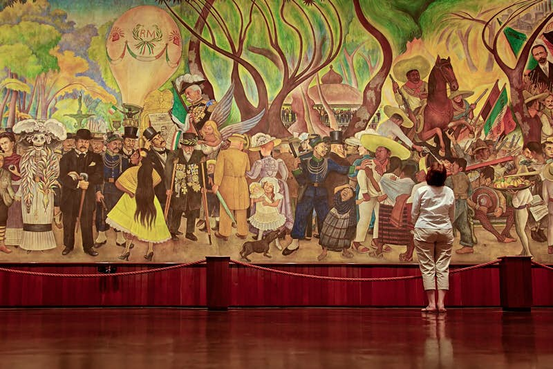 A woman stands in front of Diego Rivera's famous mural 'Dream of a Sunday Afternoon in the Alameda Central'