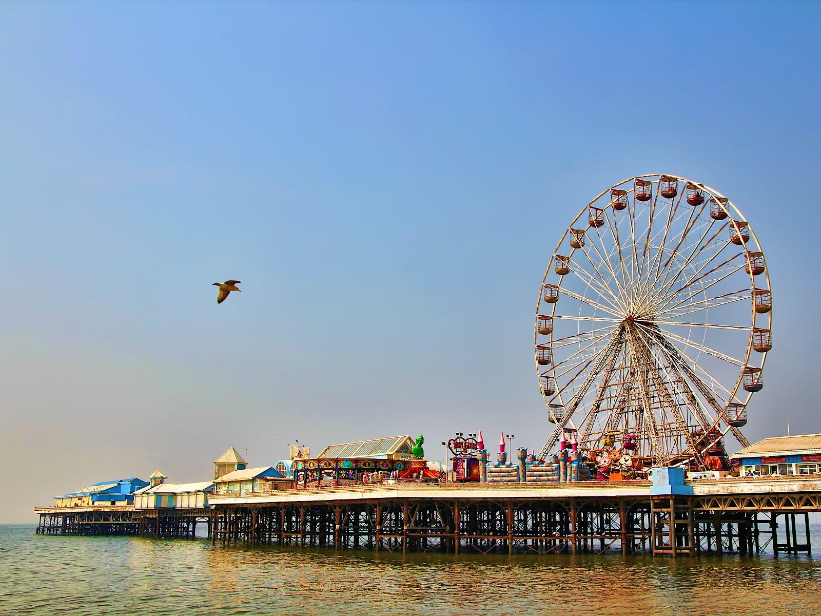 Disney alternatives - Blackpool Pleasure Beach pier. The huge ferris wheel sticks up into a clear blue sky as a seagull flies by.